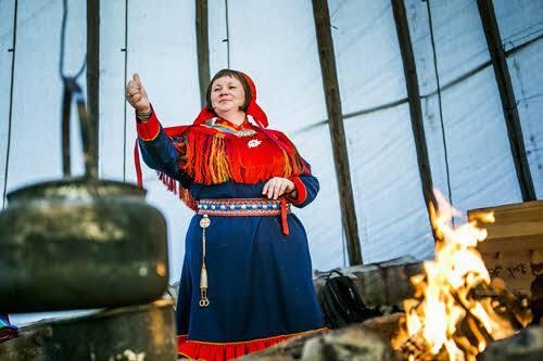 Sami woman preparing food by Christian Roth Christensen, Visit Norway
